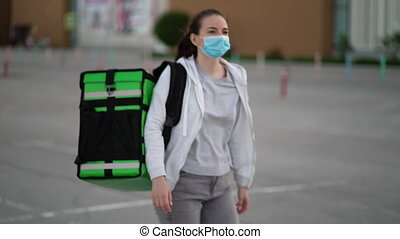 young courier wearing a medical mask is making a delivery of...