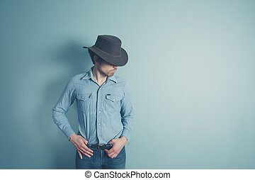 Young cowboy is standing by a blue wall