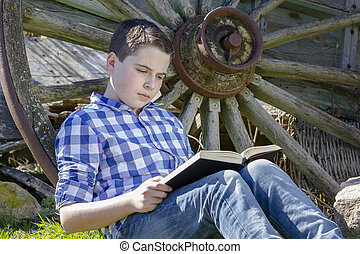 young cowboy lying beside a wagon wheel