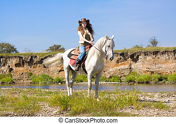 young cowgirl on white horse at the river