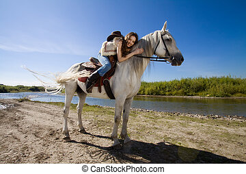 young cowgirl on white horse at the rural river
