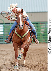Young Cowgirl - Young woman riding a horse in a rodeo race.