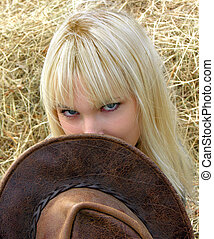 Young cowgirl - Young beautiful cowgirl near the haystack in...