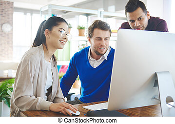 Young coworkers working on computer