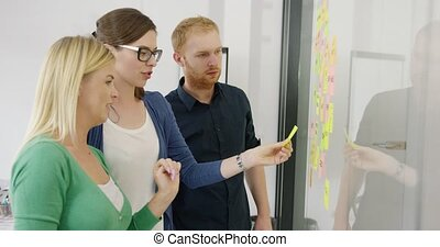 Young coworkers working on plan - Side view of two women and...