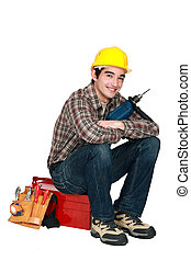 young craftsman holding a drill and sitting on a tool box