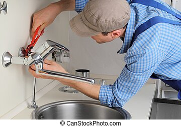 Young craftsman repairing Tap in a citchen