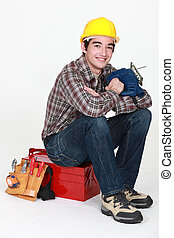 Young craftsman sitting on tool box