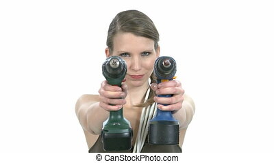 Young craftswoman with two power drills in front of white...