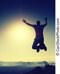 Young crazy man is jumping on rock. Silhouette of jumping man