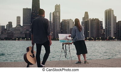Young creative couple on the shore of Michigan lake,...