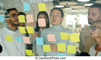Young creative men and women working with sticky notes on ...