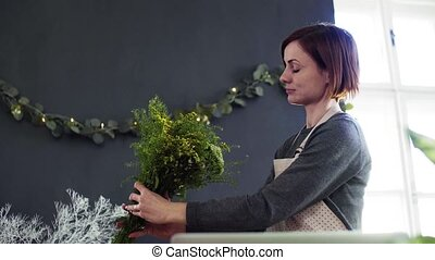 Young creative woman in a flower shop. A startup of florist...