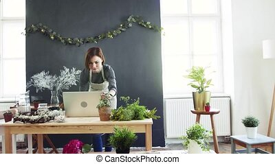 Young creative woman in a flower shop, using laptop. A...