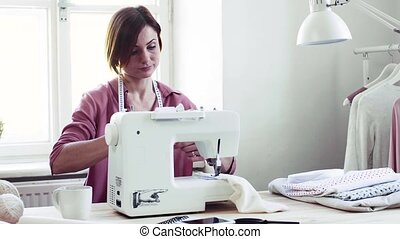 Young creative woman in a studio, working. A startup of ...