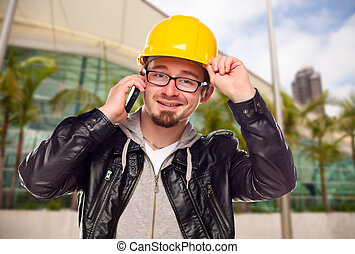Young Cunstruction Worker on Cell Phone In Front of Building