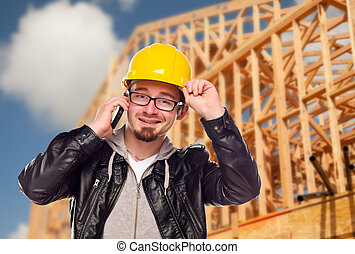 Young Cunstruction Worker on Cell Phone In Front of House