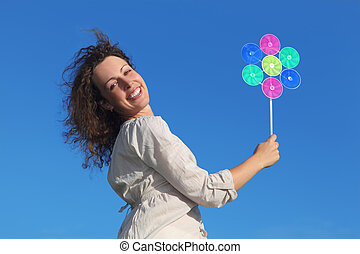young curl woman holding pinwheel toy and smiling, blue sky