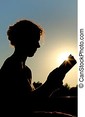 young curl woman sitting and reading book, trees and sun, ...