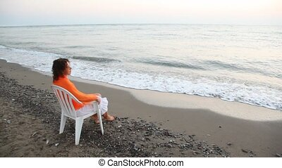 young curly-headed woman sits on plastic chair alone on beach and looks in distance pensive