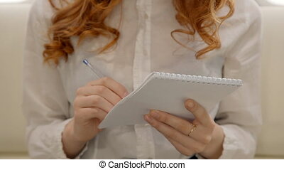 Young curly lawyer businesswoman is making notes in notebook...
