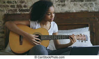 Young curly mixed race girl concentraing learning to play...