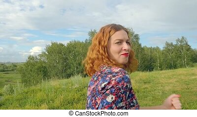 Young curly red-haired woman dancing and singing happy in summer meadow
