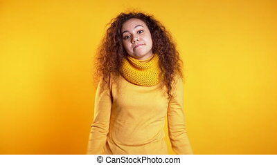 Young curly unsure girl shrugs her arms, makes gesture of I don't know, care, can't help anything .Young mixed race woman on yellow background