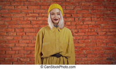 Young curly woman in total trendy yellow look. Portrait of flirting beautiful girl on orange bricks wall studio background.