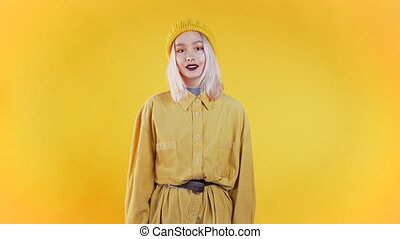Young curly woman in total trendy yellow look. Portrait of flirting beautiful girl on studio background.