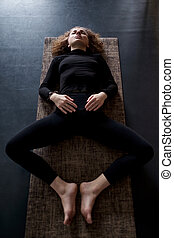 woman practicing in a yoga studio resting in shavasana or corps pose