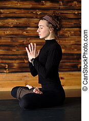 woman practicing yoga, sitting in Padmasana exercise, Lotus pose