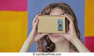 Young curly woman using Virtual Reality Glasses. Google cardboard