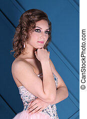 Young curly woman with makeup poses with earrings in blue studio