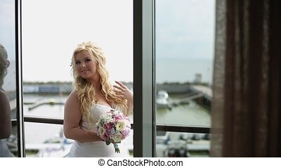 Young curvy woman in lingerie with bouquet on balcony