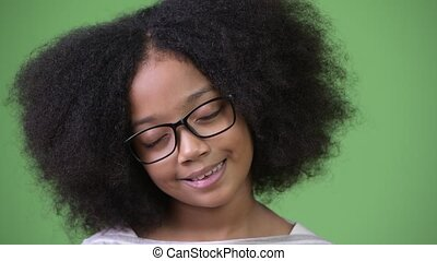 Young cute African girl with Afro hair relaxing with eyes closed