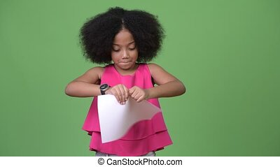 Young cute African girl with Afro hair ripping paperwork
