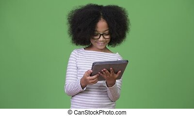 Young cute African girl with Afro hair using digital tablet