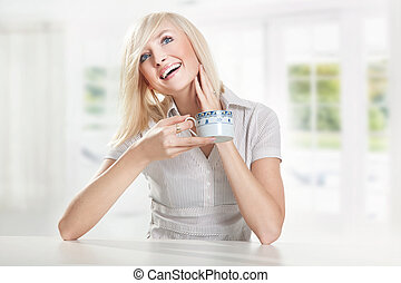 Young cute blonde drinking coffee