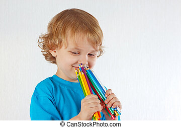 Young cute boy holds color pencils on a white background