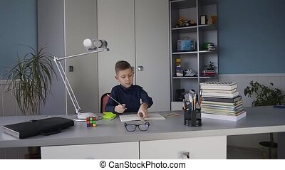 Young cute boy in a blue shirt sitting at a desk in his room and doing a homework. Books on the table, homework