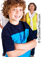 Young cute boy in focus with family in the background