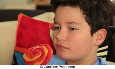 Young cute boy with big colorful lollipop candy