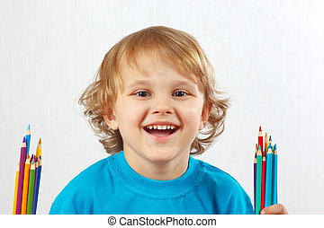 Young cute boy with color pencils on a white background