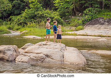 Young cute boys playing in the water in a beautiful river on a sunny summer day. Childhood in nature