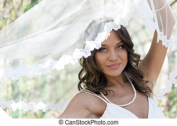 Young cute bride posing with a veil