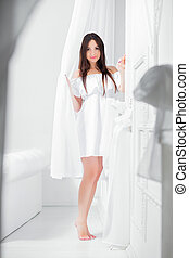 Young cute brunette dressed in a white dress.