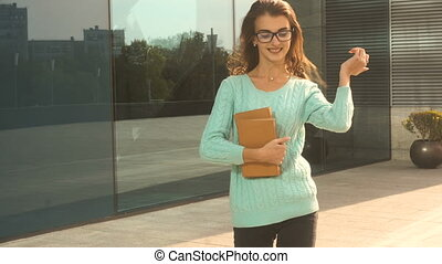 young cute brunette in glasses walking in the street with...