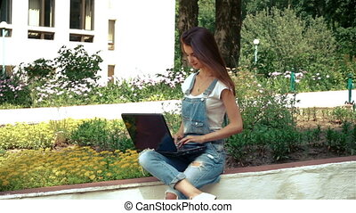 cute brunette in jeans jumpsuit sitting on the street and looking at laptop