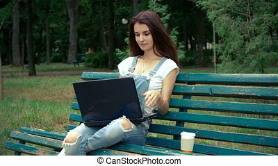 young cute brunette sitting on a bench with laptop smiling...